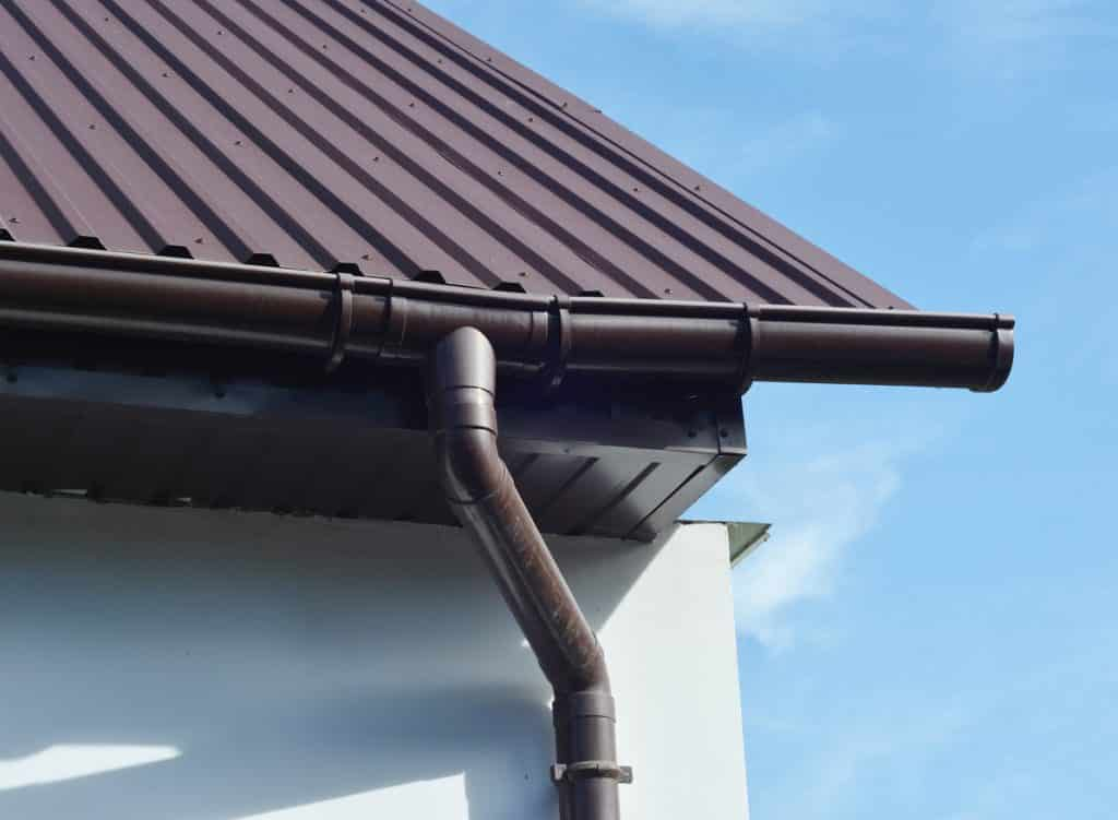 A close-up on a part of a house exterior white wall with brown metal roof, eaves, fascia boards, soffit, and a rain gutter system with a downspout against blue sky.